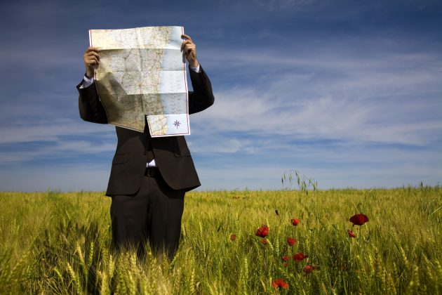 businessman lost in field using map