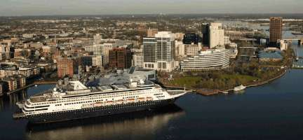 A cruise ship rests in the harbor at the National Maritime Center.